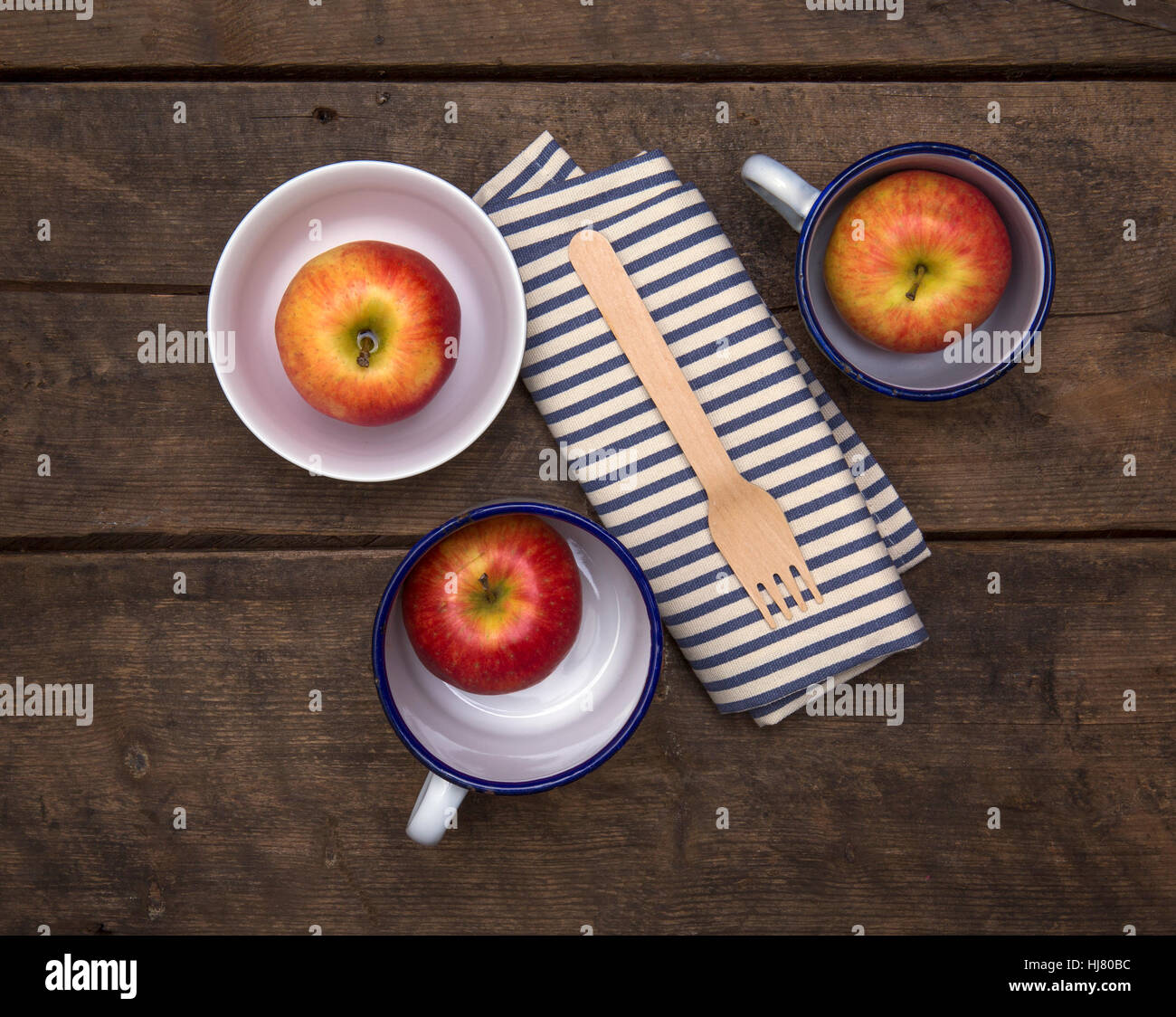 Apples in Bowls with fork and napkin on a rustic wooden table - Stock Image