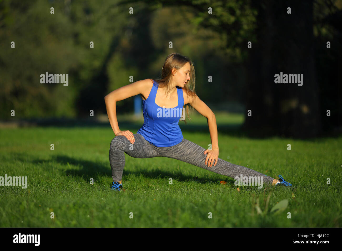 Beautiful young woman doing thrust in park - Stock Image
