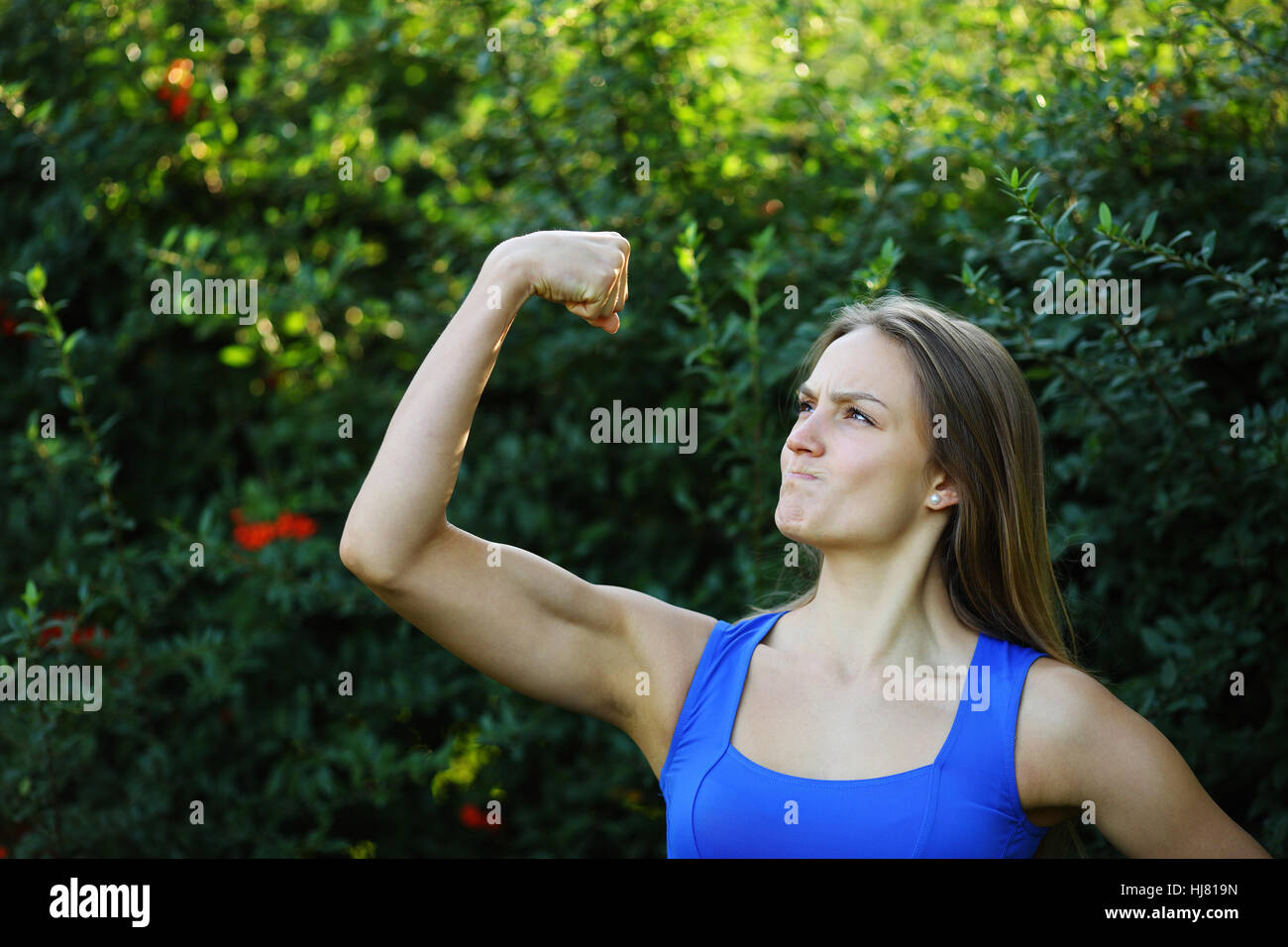 Beautiful fitness girl muscle strain on arm in nature - Stock Image