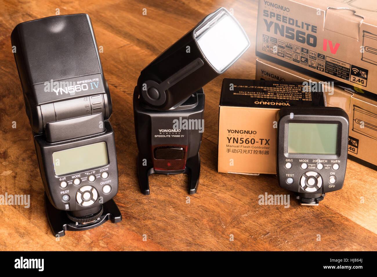 New Yongnuo YN560 IV speedlite set with wireless YN560-TX trigger on wooden table - Stock Image