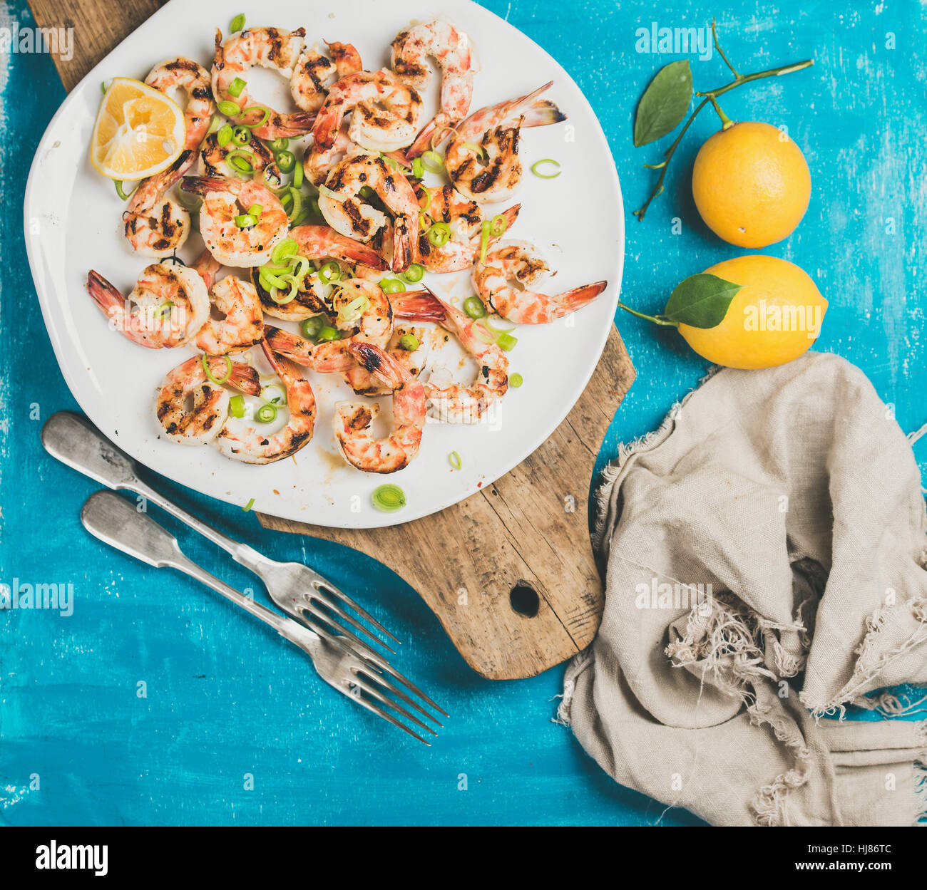 Grilled tiger prawns in white plate with lemon, leek, chili - Stock Image