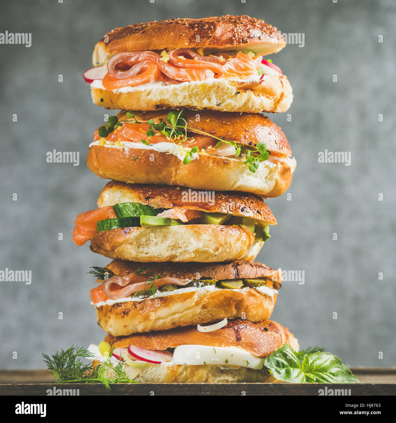 Close-up of Bagels heap with smoked salmon, eggs, vegetables, cream-cheese - Stock Image