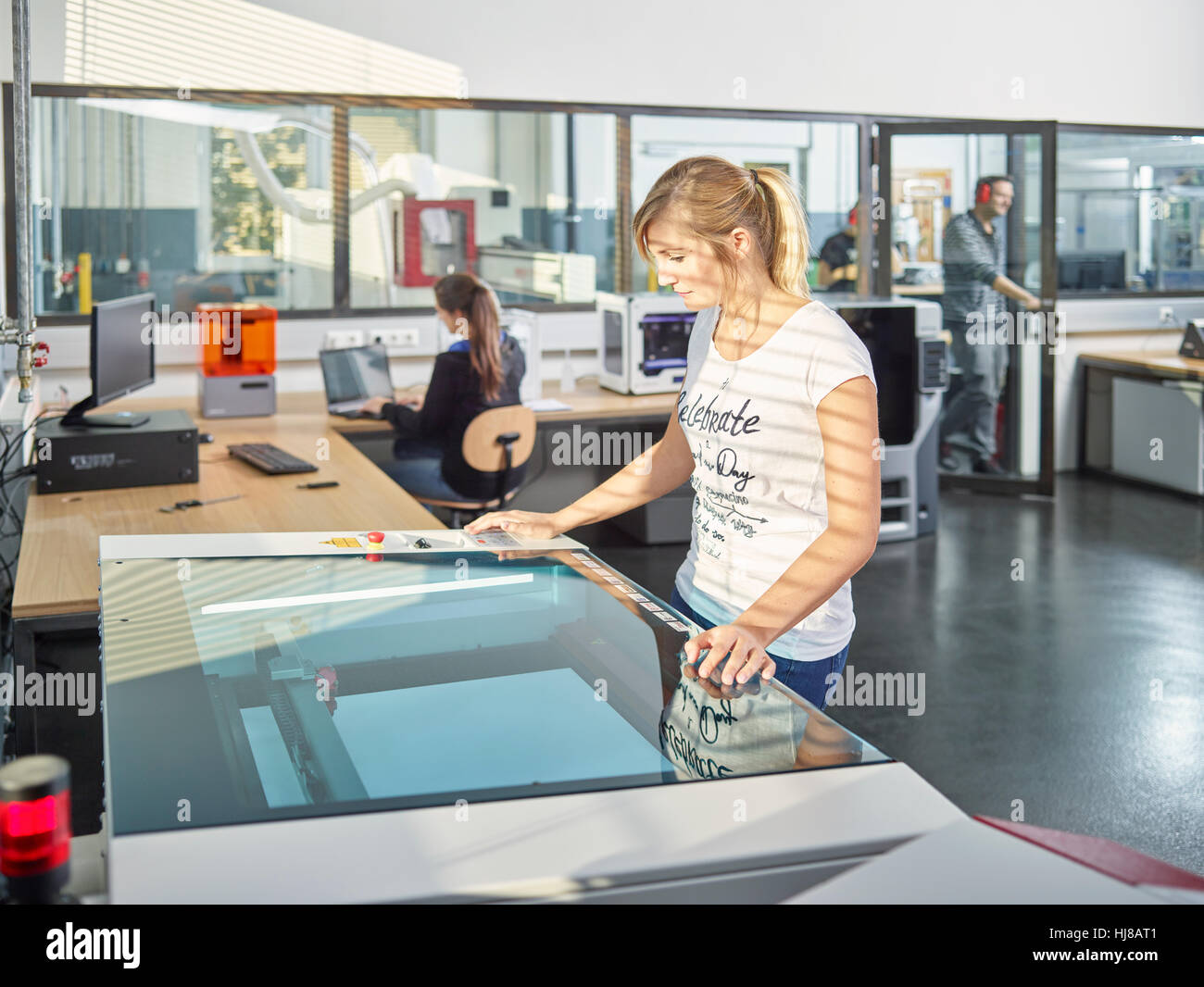 Woman in workshop with laser cutter, Austria - Stock Image