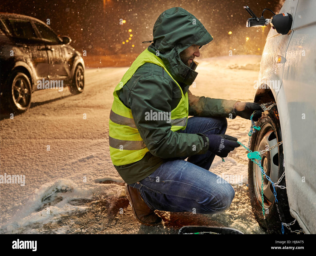 Man with safety vest applying snow chains on snow-covered road, Wattens, Tyrol, Austria Stock Photo
