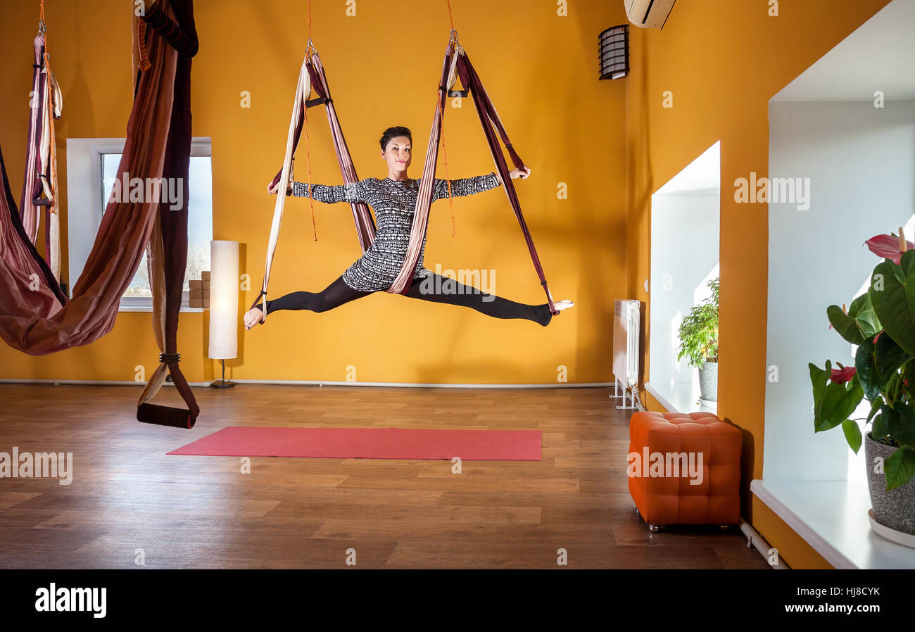 Young woman doing antigravity yoga leg split position at wellness studio with yellow walls - Stock Image