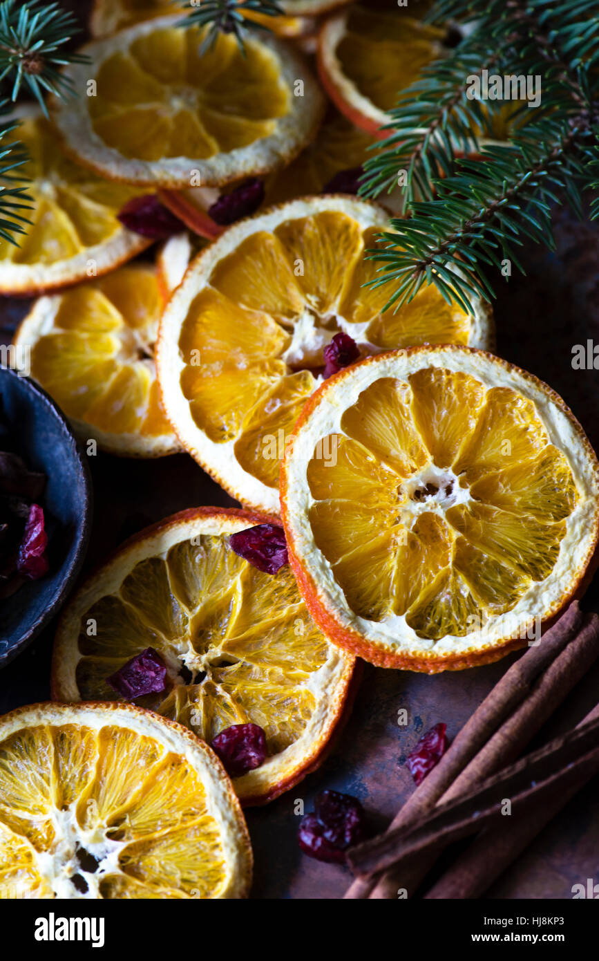 Slices of dried oranges with cinnamon sticks and fir tree branches - Stock Image