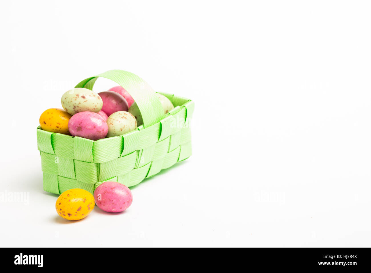 Colourful easter eggs in a green wicker basket on white background Stock Photo
