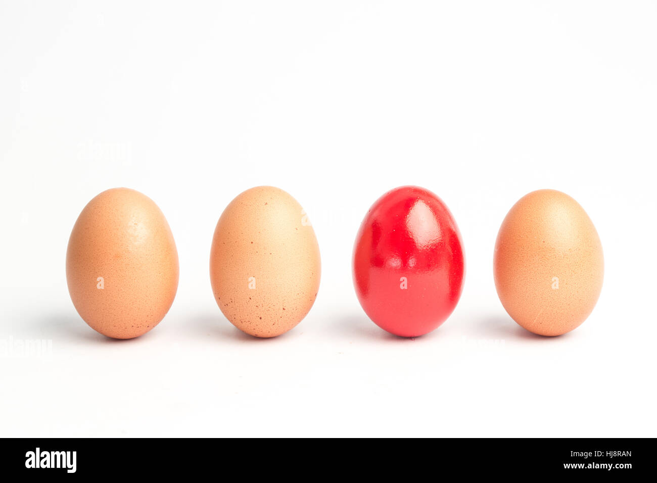 Four eggs in a row with one red one on white background - Stock Image