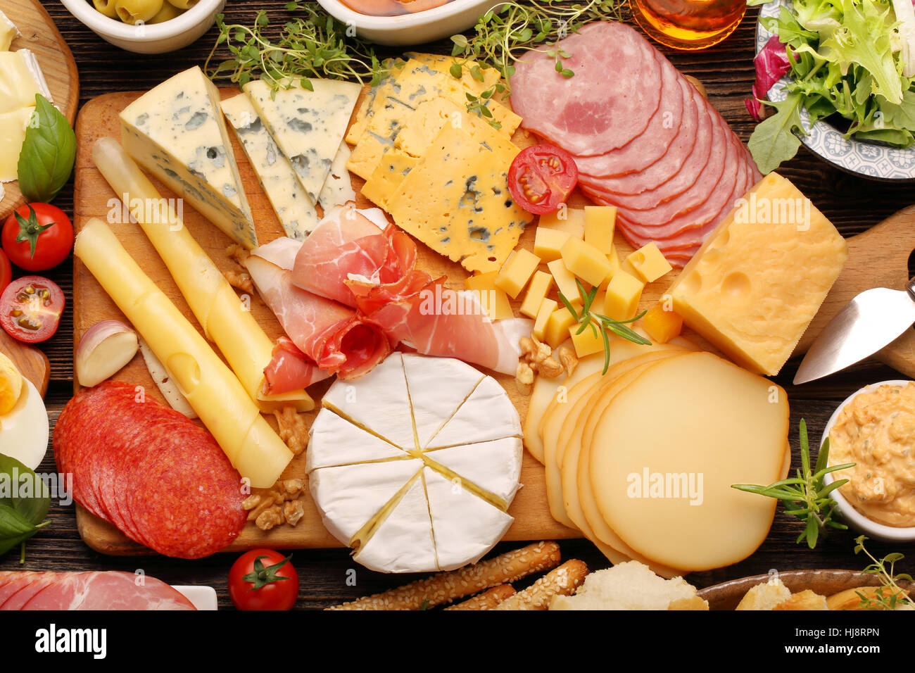 buffet of various types of cheese and appetizers set on rustic wooden board - Stock Image