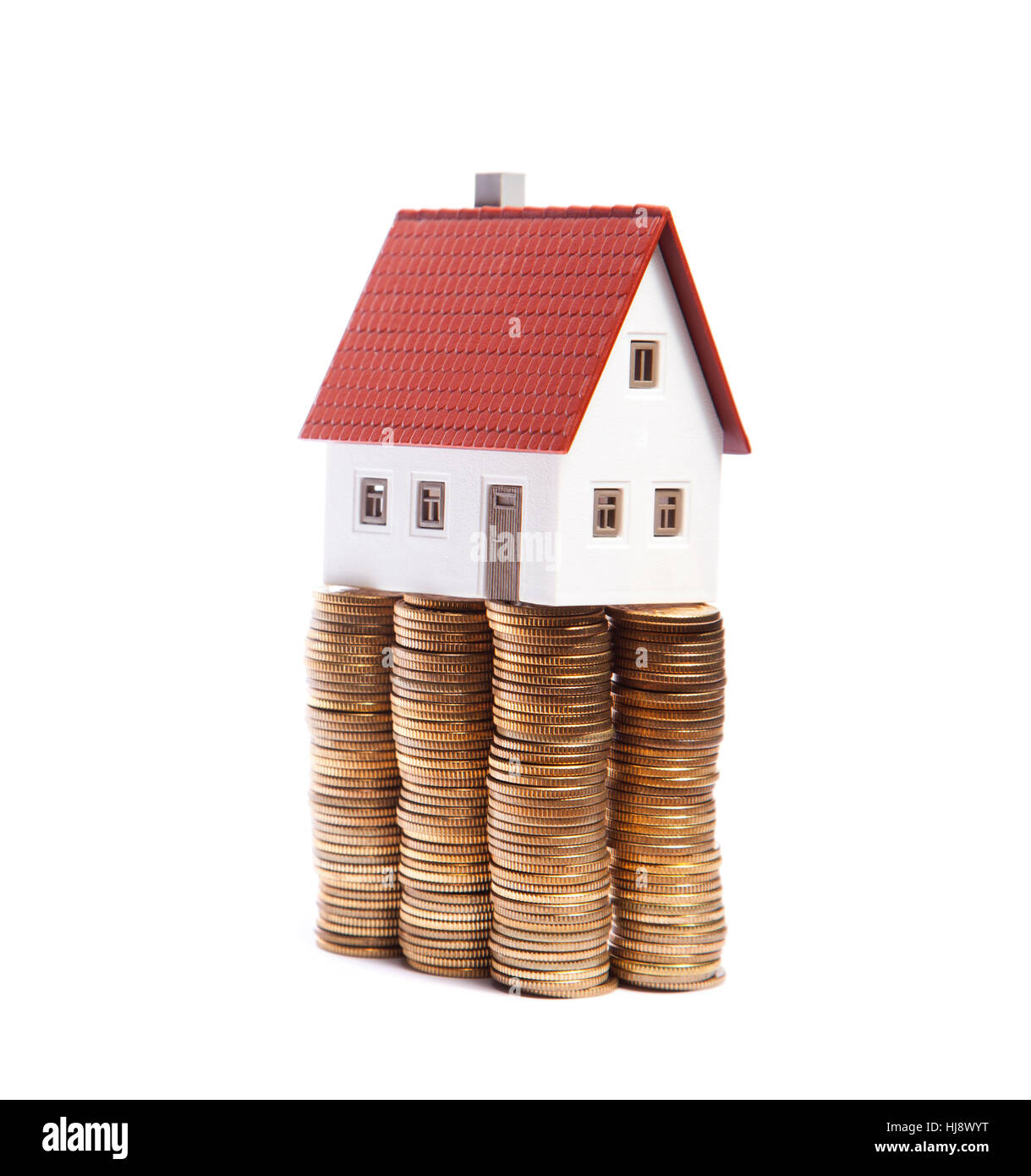 House miniature on stacks of golden coins on white background - Stock Image