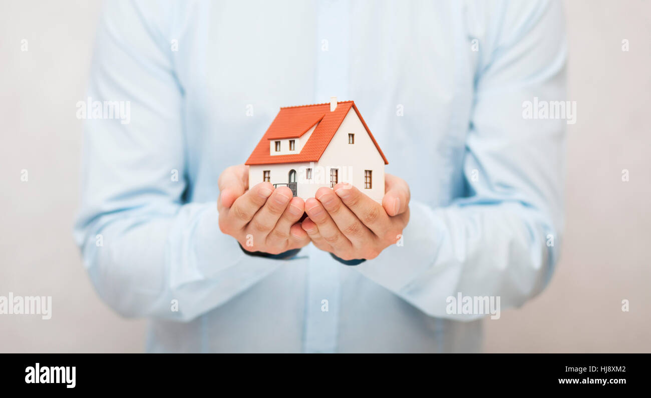Small toy house in hands - Stock Image