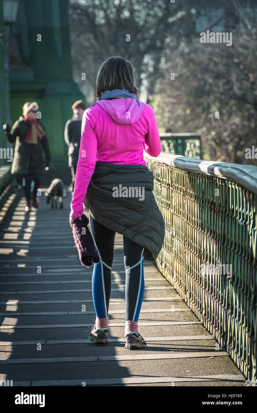 A woman in a pink top and tracksuit bottoms walking accros a bridge - Stock Image