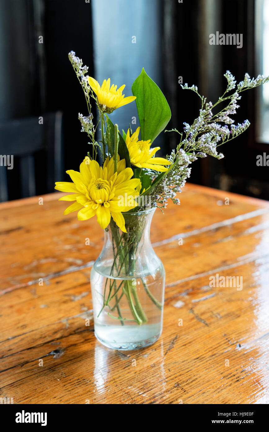 Glass Bud Vase With Yellow and White Flowers on a Rustic Wooden ...
