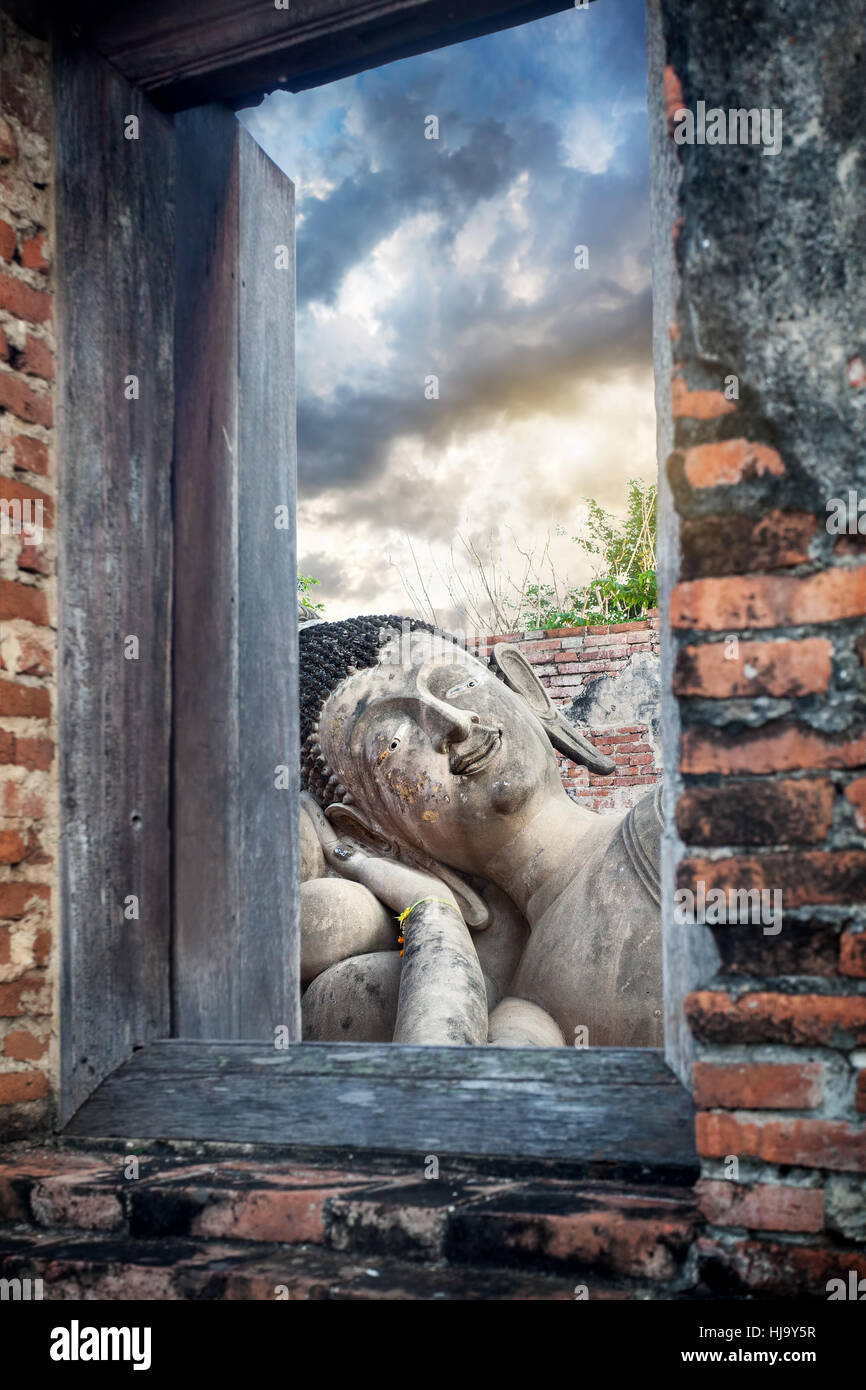 Sleeping Buddha statue and ruined temple in Ayutthaya ancient capital of Thailand Stock Photo