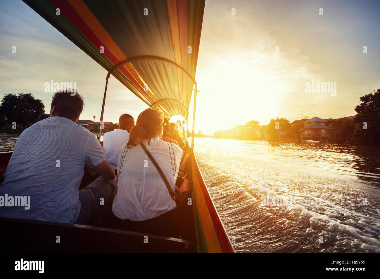 Tourist sitting in long-tail boat cruise by Chao Phraya river in Ancient city Ayutthaya at Sunset, Thailand - Stock Image