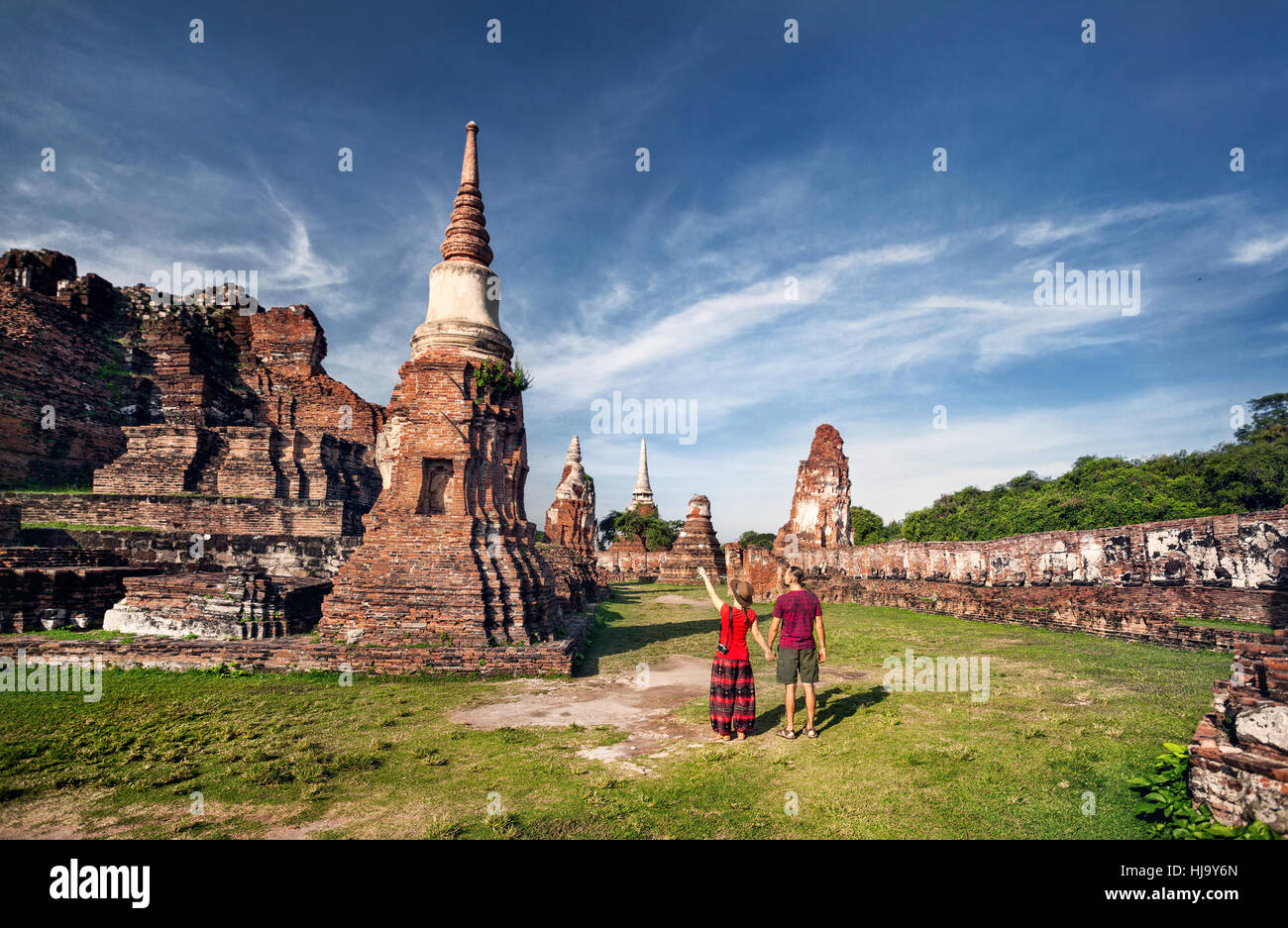Young Couple in red clothes with photo camera looking at ancient ruined Wat Mahathat in Ayutthaya, Thailand - Stock Image