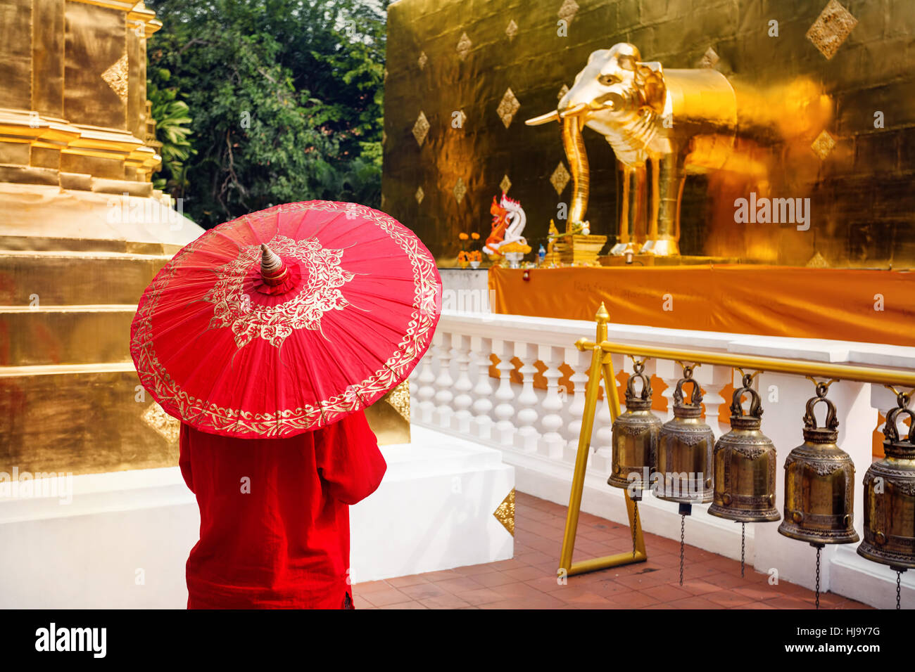 Woman tourist with red traditional Thai umbrella in Golden temple Wat Phra Singh in Chiang Mai, Thailand - Stock Image