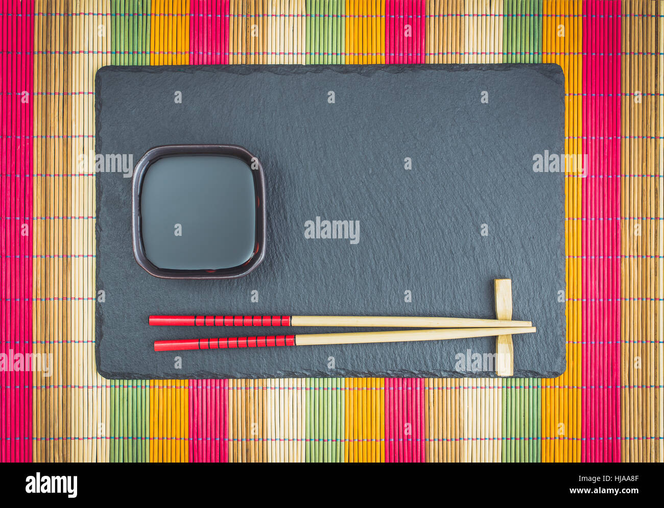 Chopsticks  and soy sauce on slate top view - Stock Image