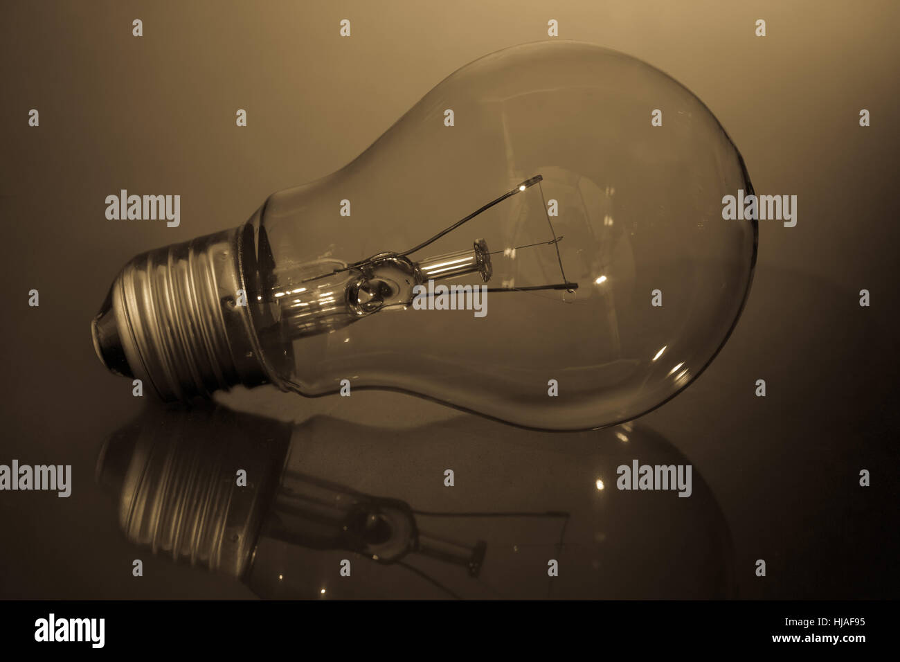 Clear light bulb laying on its side on reflective surface in sepia tones - Stock Image