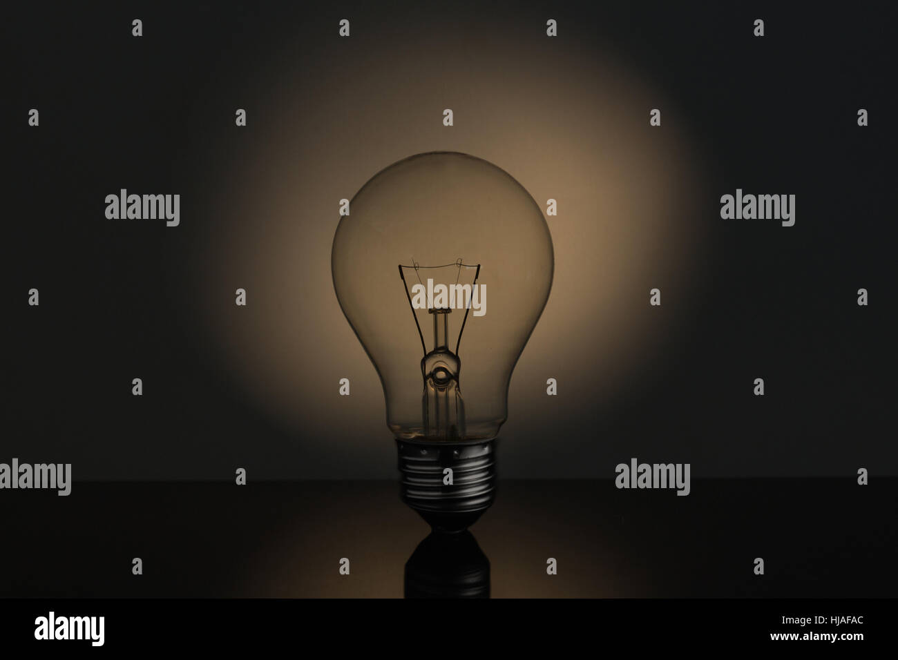 Big light bulb standing in sepia tones on reflective black surface - Stock Image
