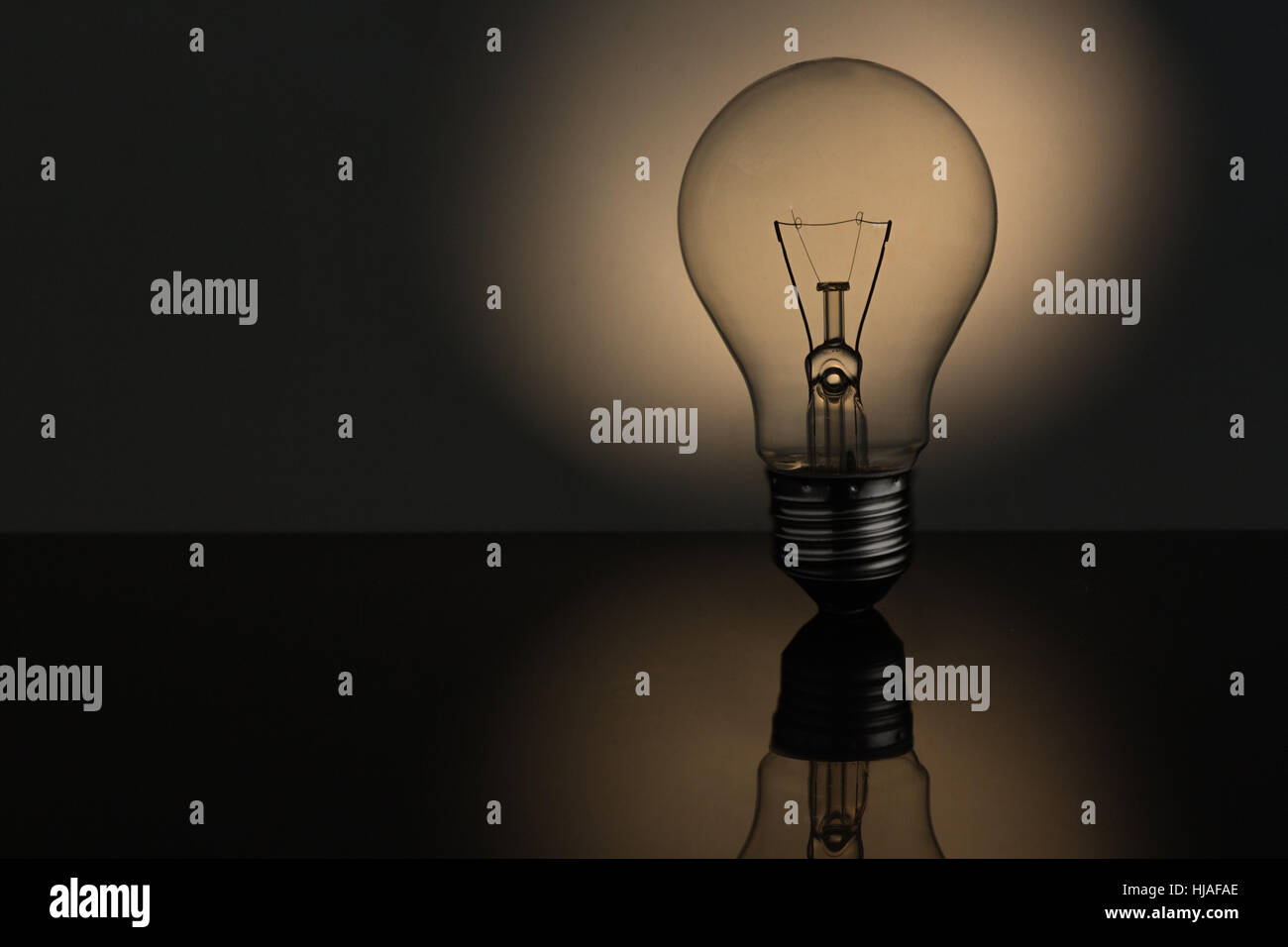 Filament light bulb with copy space in sepia tones - Stock Image