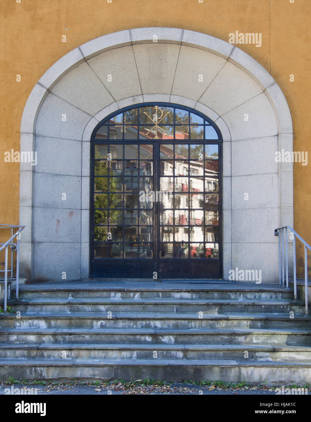 Arched main doorway ,entrance to Iladalen church in Oslo Norway, glass doors reflecting apartment blocks and surroundings, - Stock Image