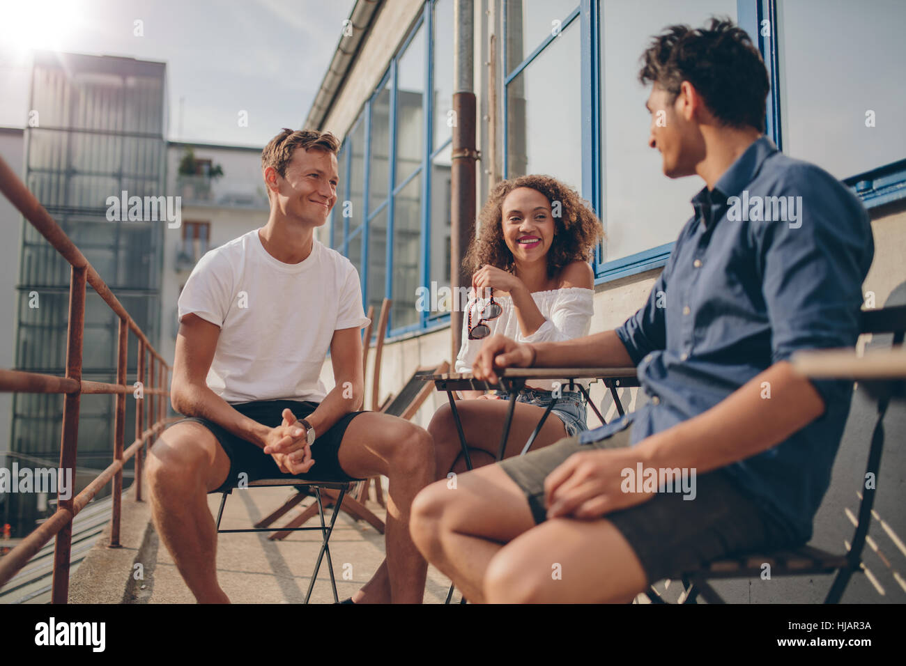 Three young friends together at outdoor cafe. Multiracial group of young people sitting around a small cafe table - Stock Image