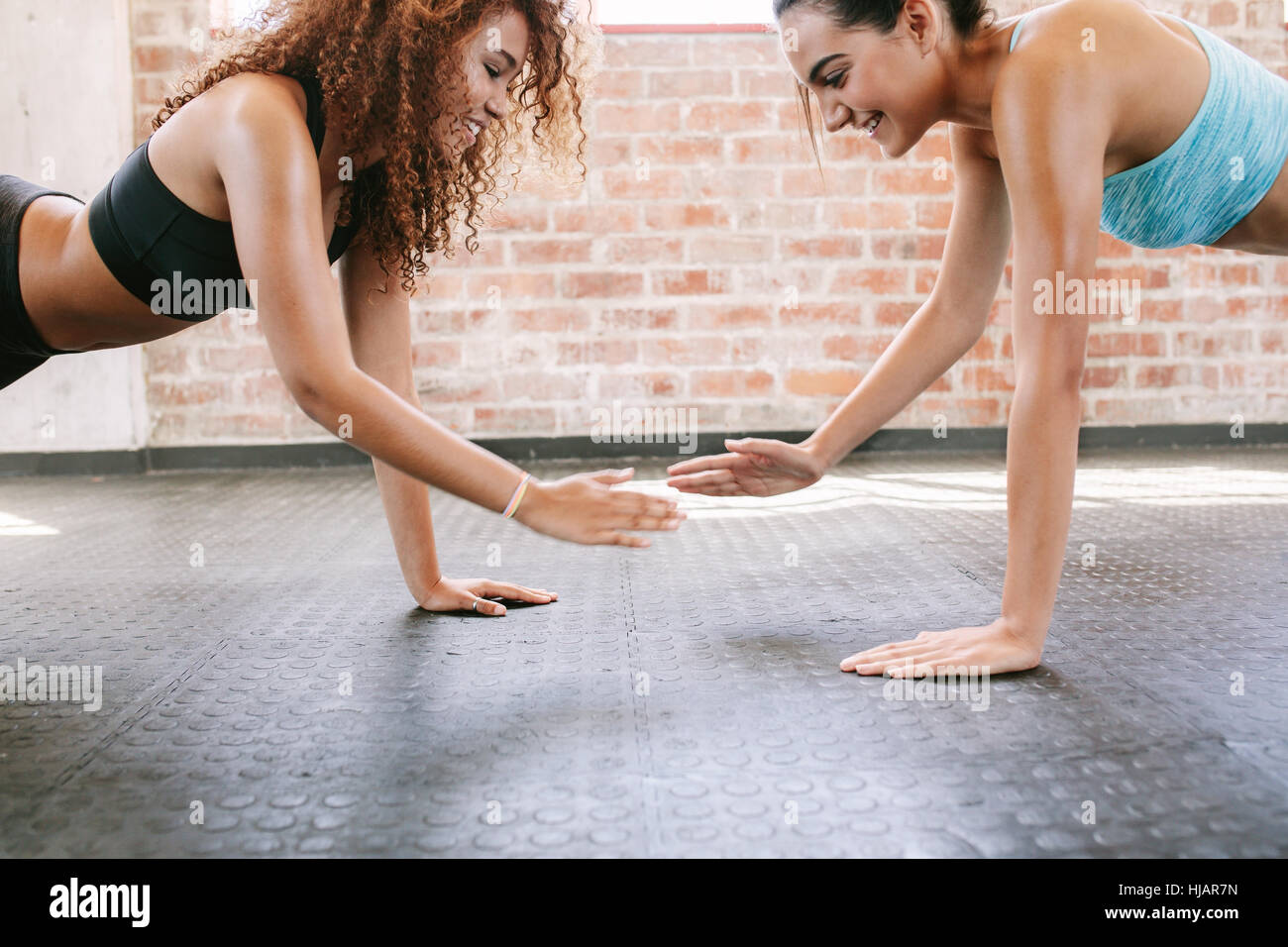 Side view shot of two young female exercising together in gym. Women doing pushups together. - Stock Image