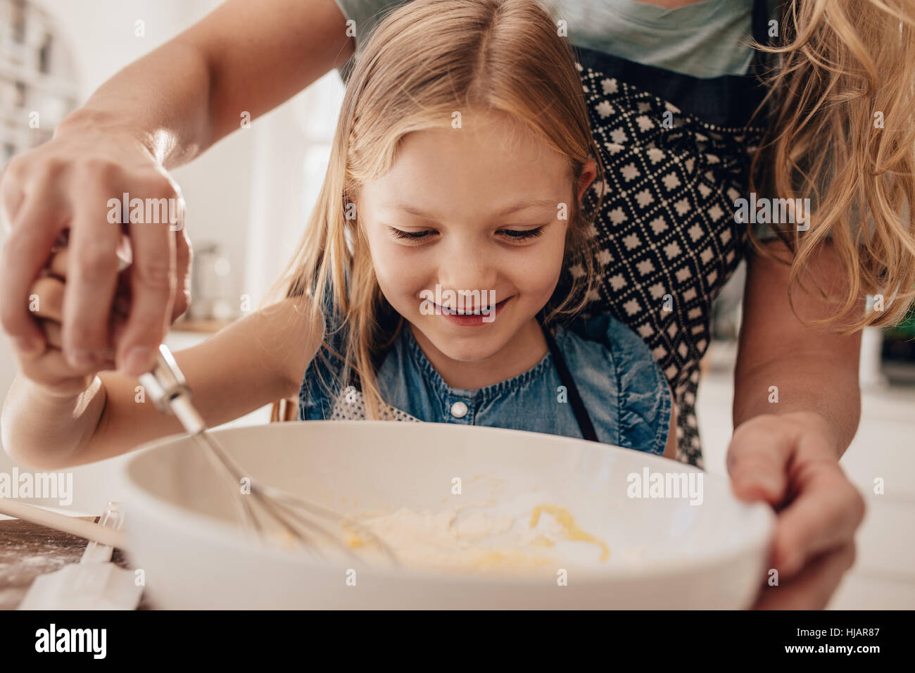 Beautiful little girl with her mother mixing batter in bowl and smiling. Mother and daughter in kitchen preparing - Stock Image