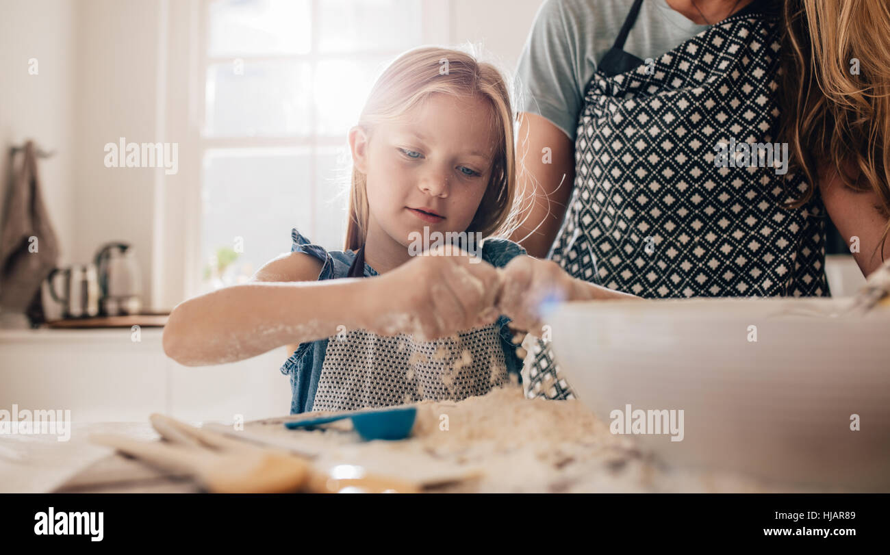 Cute little girl preparing dough in kitchen with her mother. Young girl learning to cook. - Stock Image