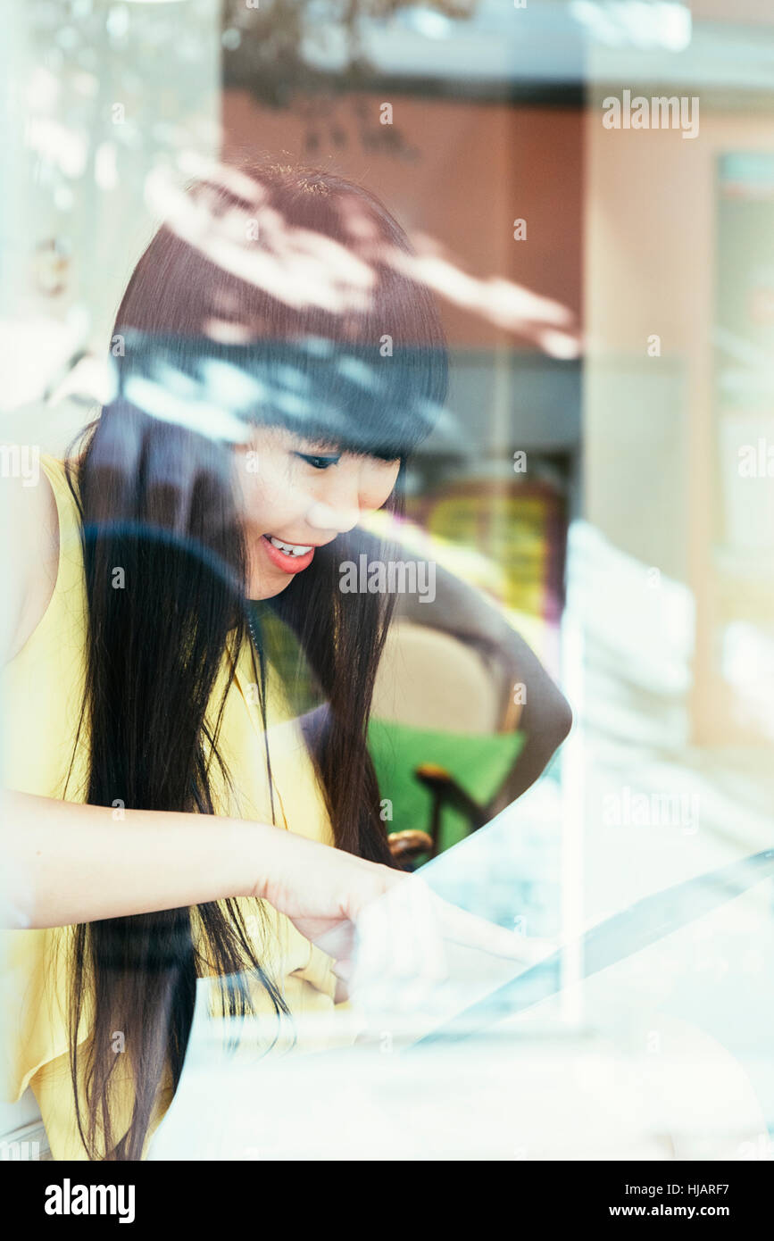 Chinese Businesswoman using technology sitting at cafe - Stock Image