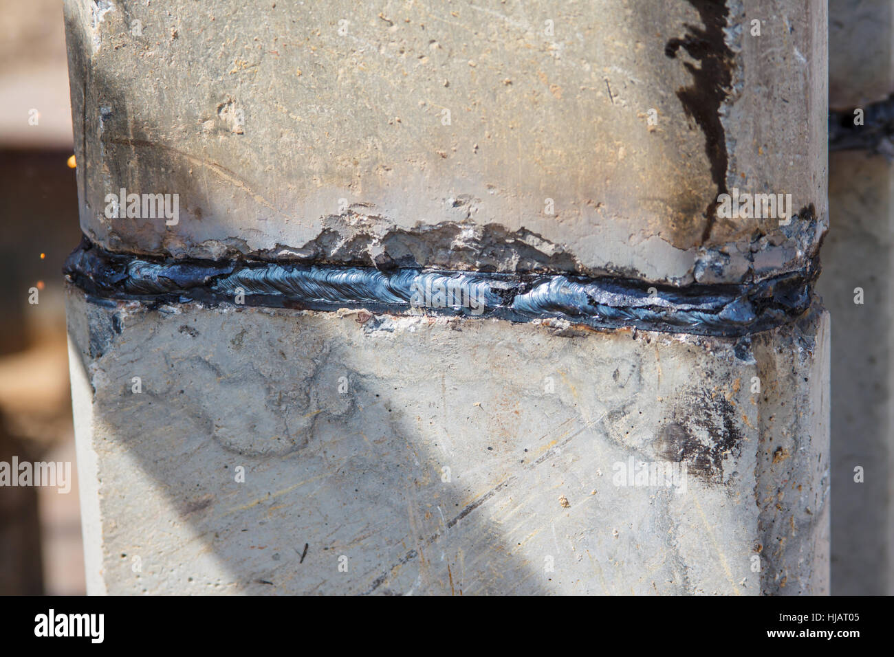 Welding joint on finished concrete pilings Stock Photo