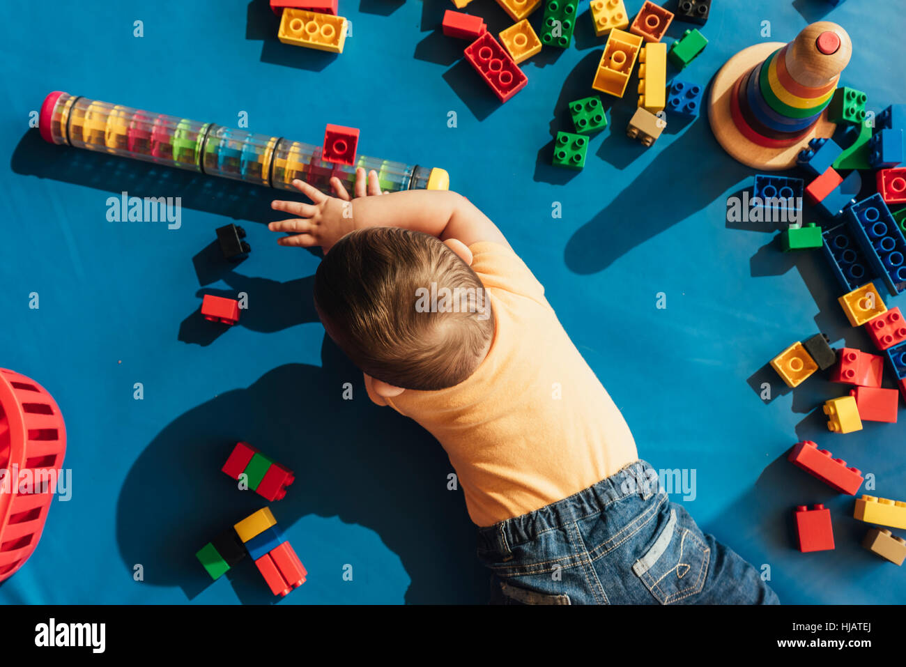 Happy baby playing with toy blocks in the kindergarten. - Stock Image