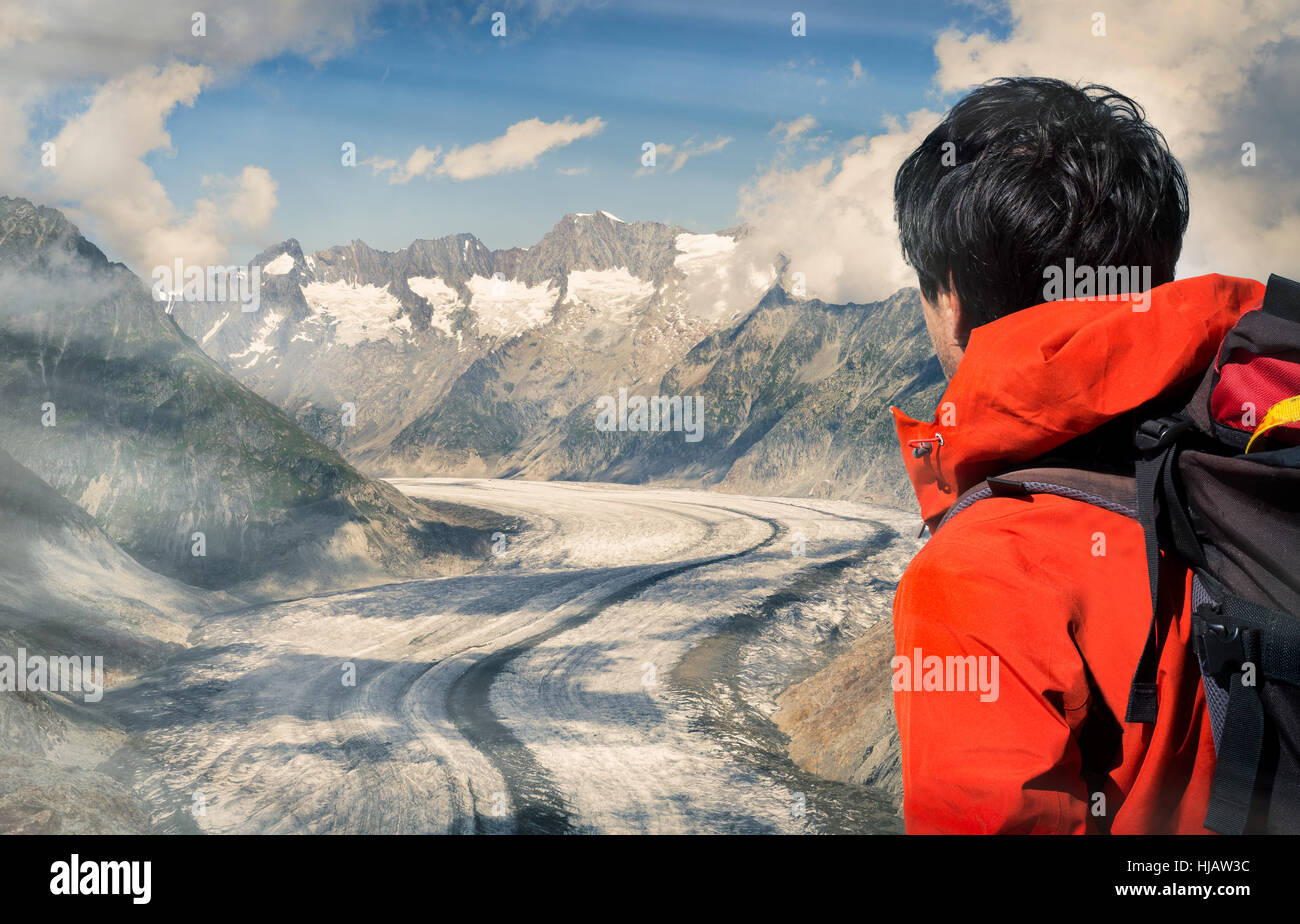 Lone male climber looking out over Aletsch Glacier, Canton Wallis, Switzerland - Stock Image