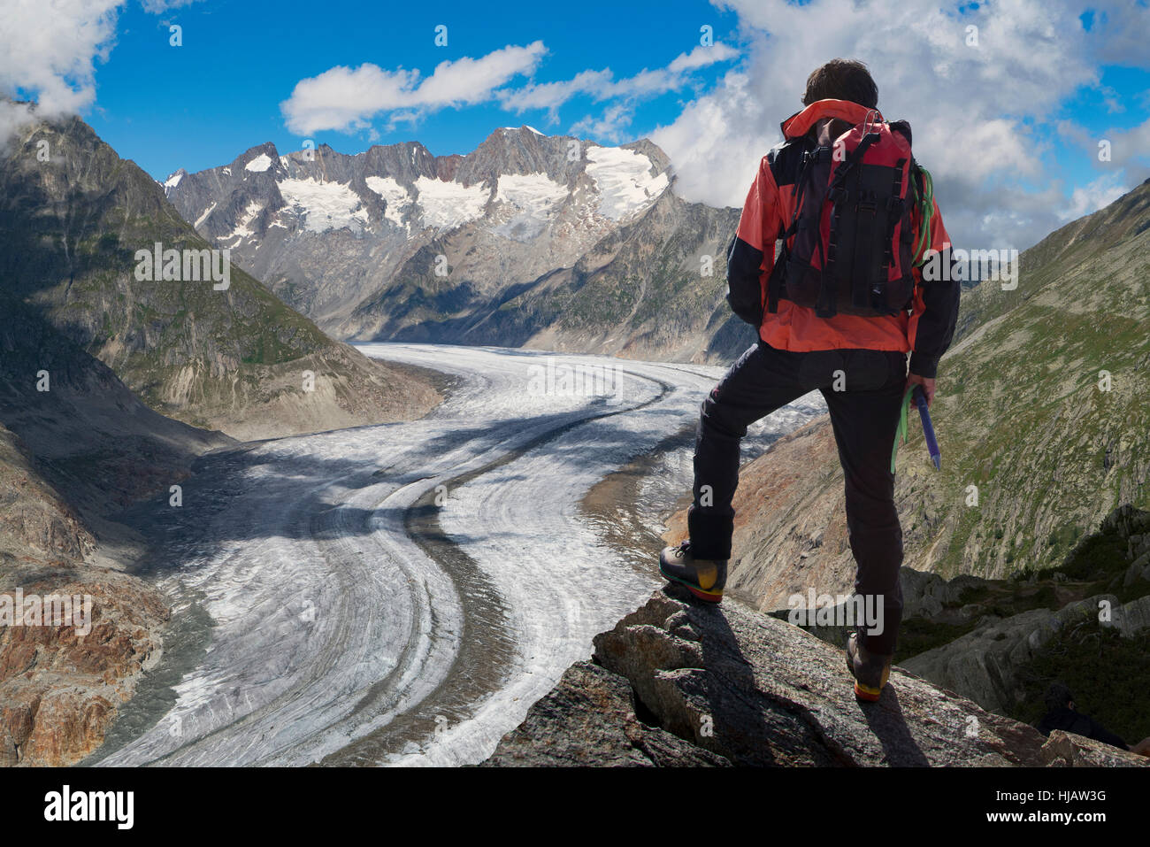 Rear view of lone male climber looking out over Aletsch Glacier, Canton Wallis, Switzerland - Stock Image