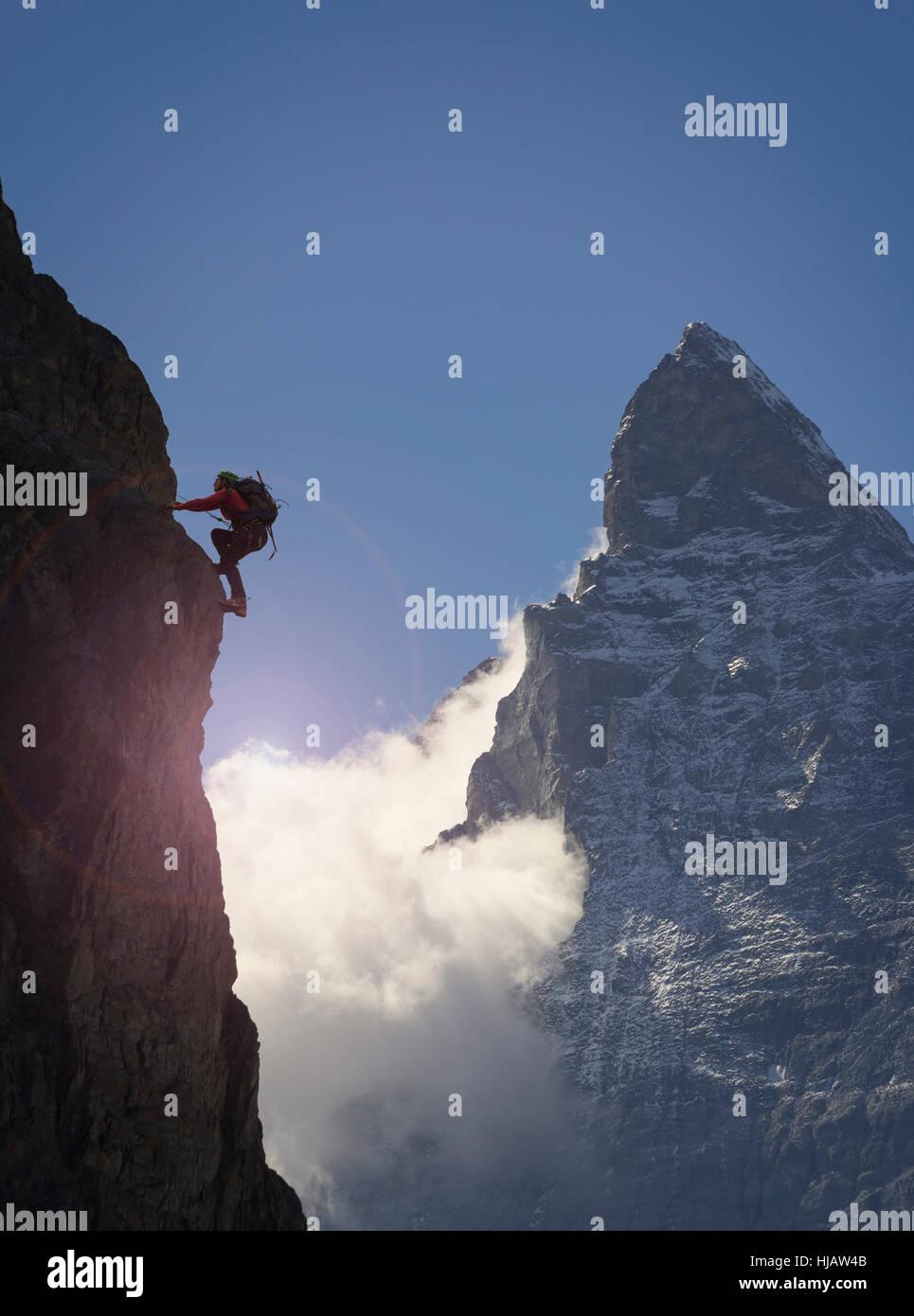 Silhouetted female climber climbing rock face near Matterhorn, Canton Wallis, Switzerland Stock Photo