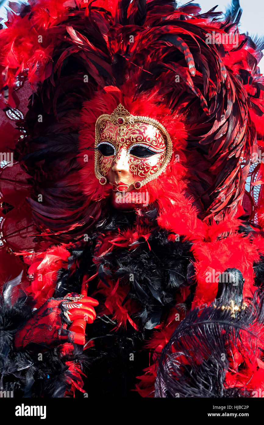 Participant in colorful red costume and mask during traditional famous Carnival in Venice, Italy. - Stock Image