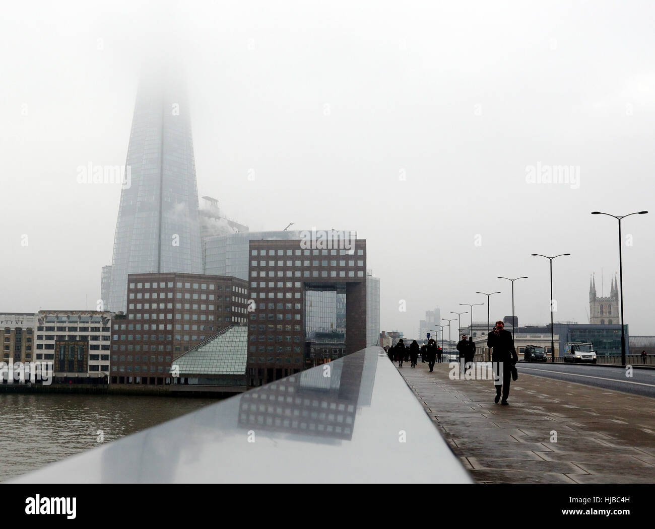 Pedestrians cross London Bridge with the Shard shrouded in fog behind them, as dense fog caused travel disruption Stock Photo