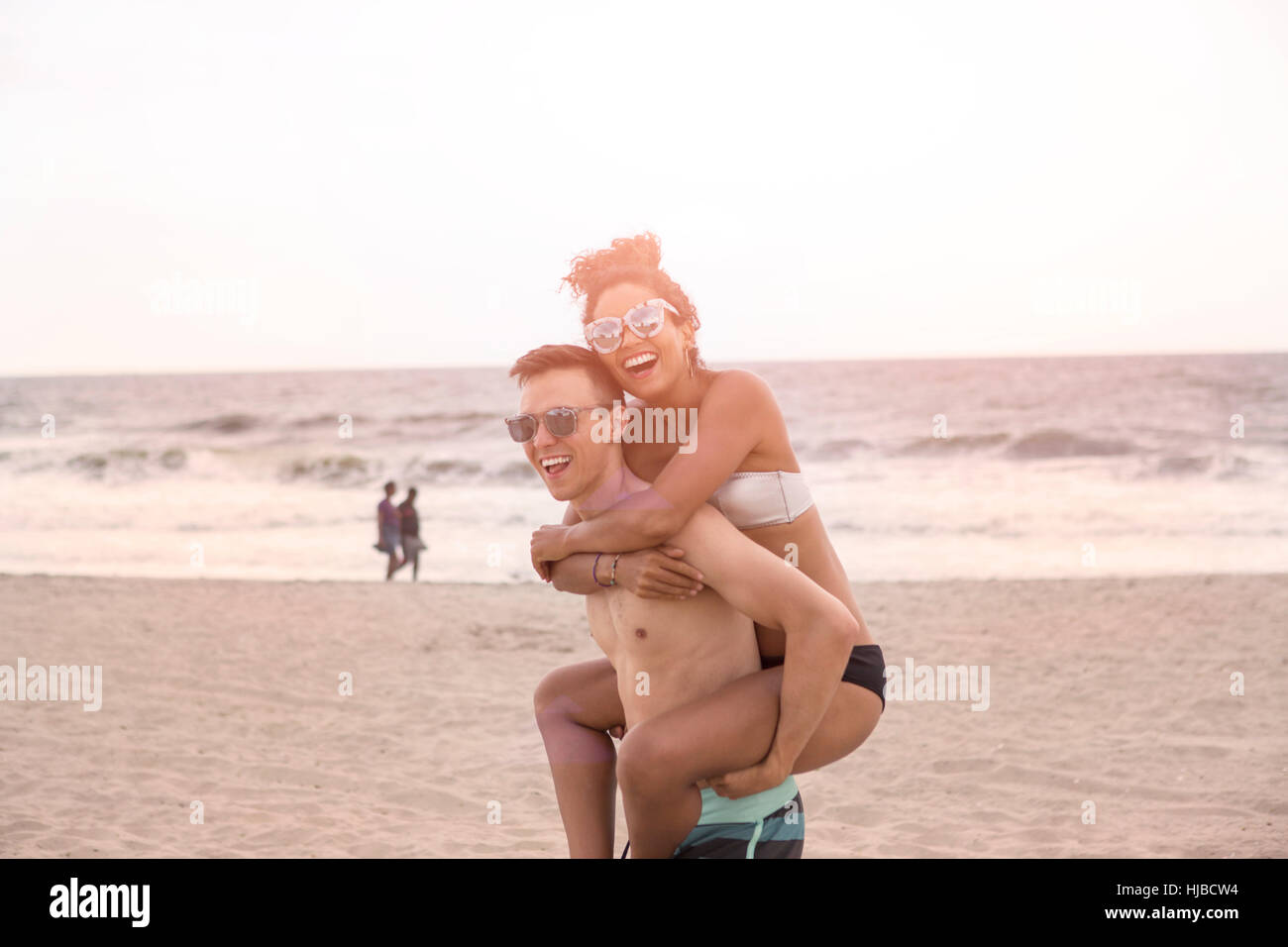 Young man giving piggy back to girlfriend on Rockaway Beach, New York State, USA - Stock Image