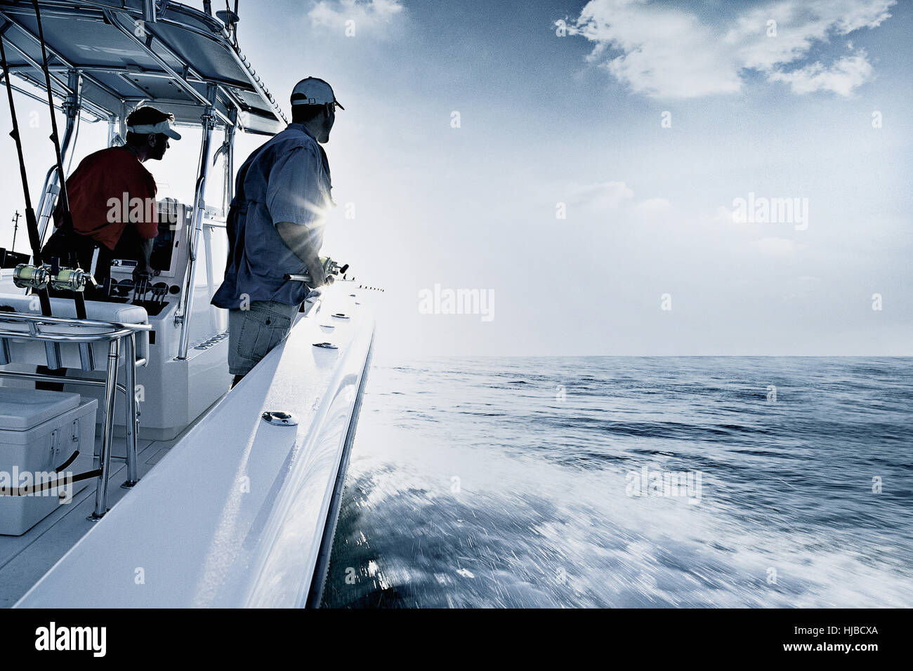 Monochromatic shot of two men driving and fishing from speedboat, Miami, USA - Stock Image