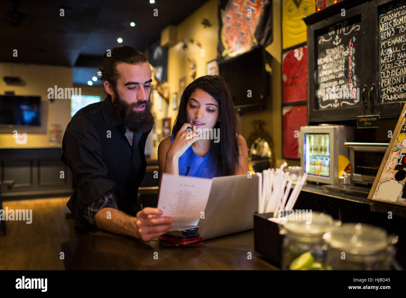 Young couple reading menu at public house table Stock Photo