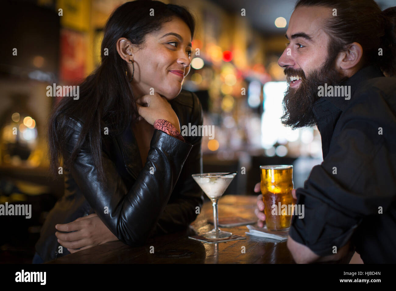 Romantic young couple with cocktail and beer in public house - Stock Image