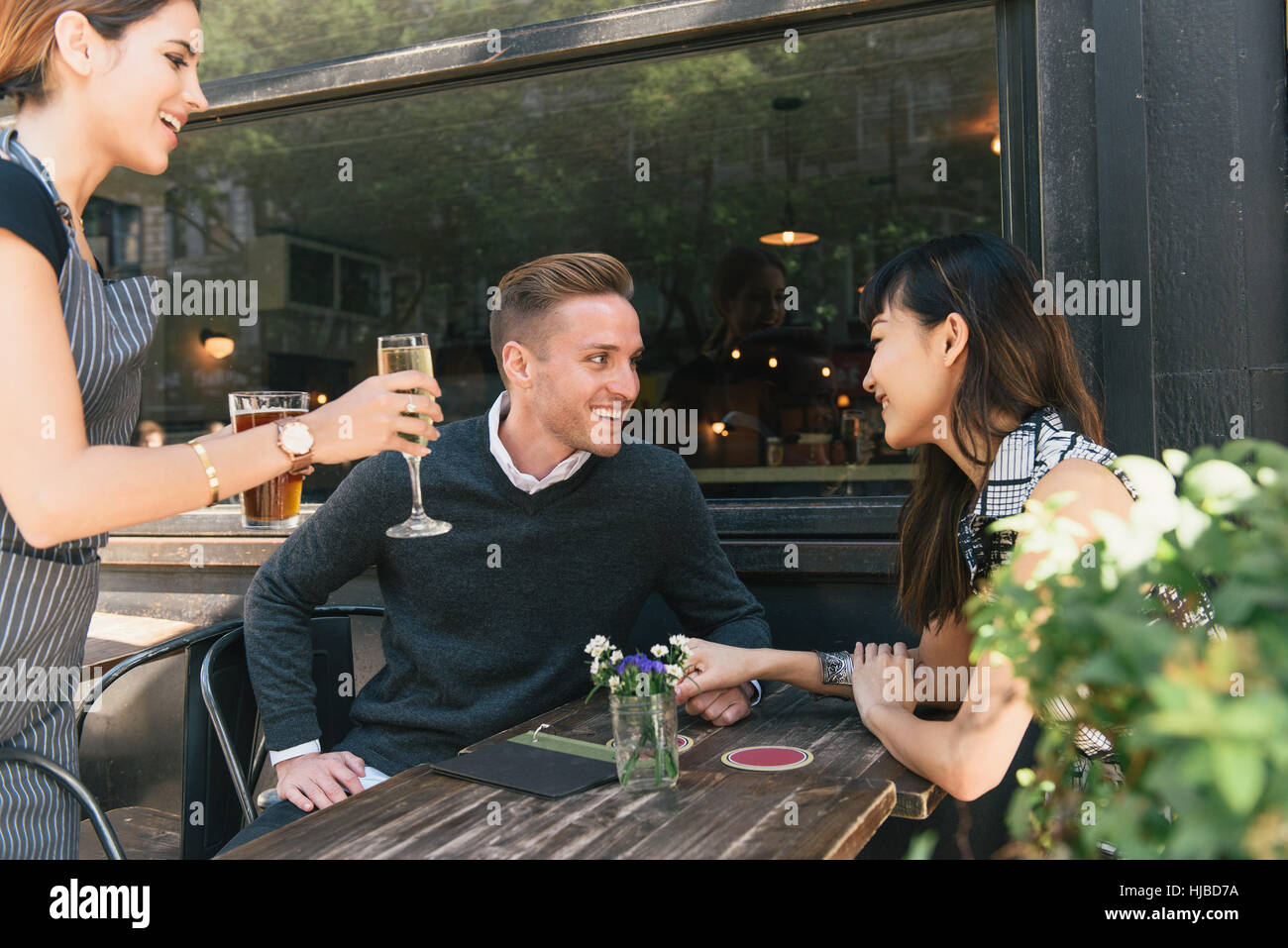 Young couple sitting outside bar, being served drinks by bar worker - Stock Image