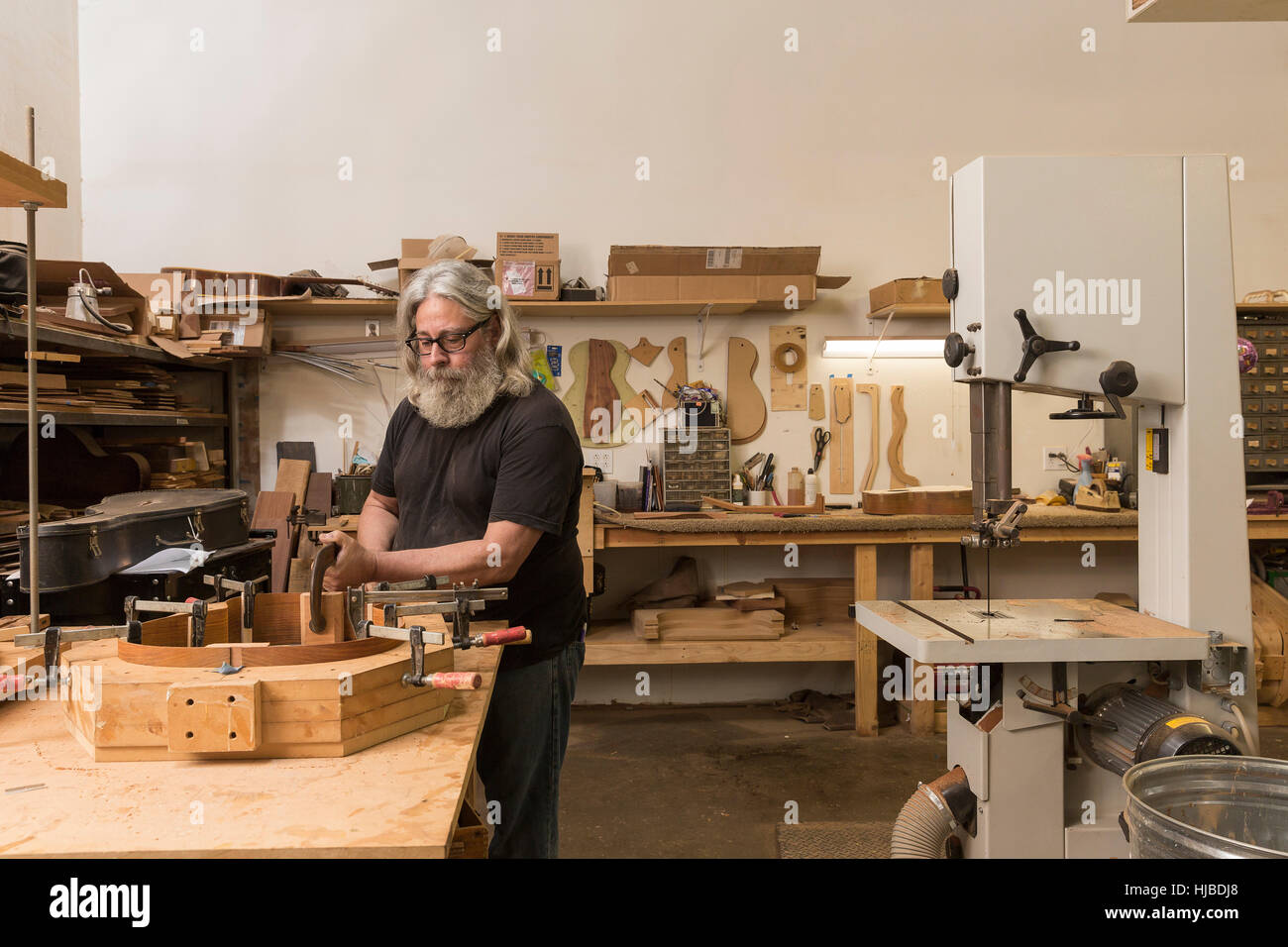 Guitar maker in workshop manufacturing guitar - Stock Image