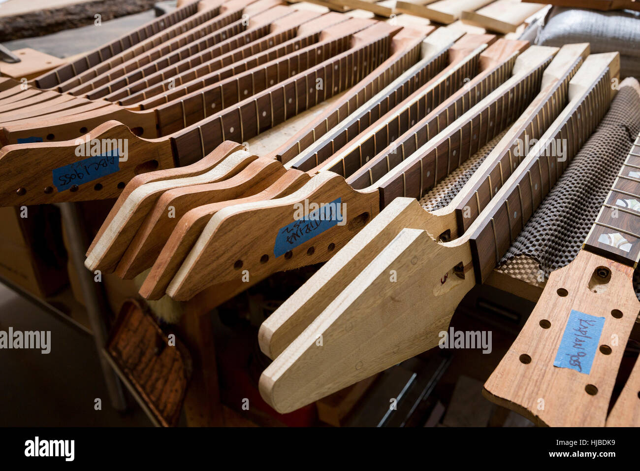 Headstocks and necks of guitars in workshop - Stock Image