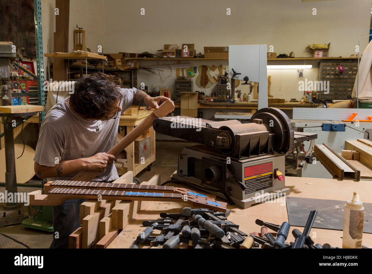 Guitar maker manufacturing guitar in workshop - Stock Image