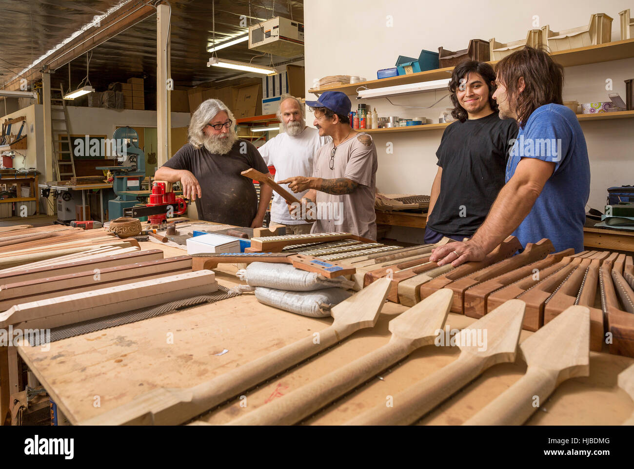 Guitar makers in workshop quality checking guitar necks - Stock Image