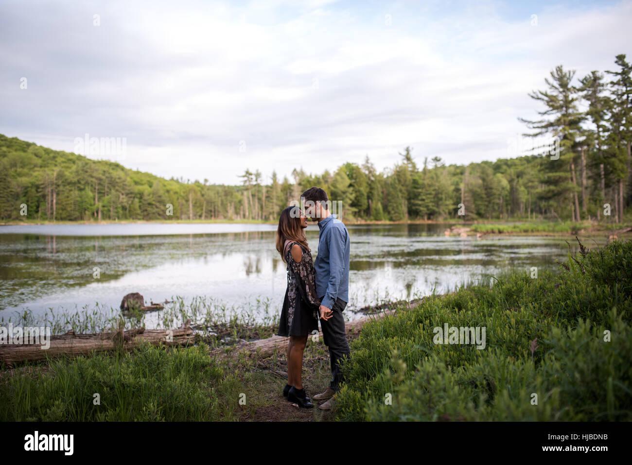 Couple rubbing noses by lake, Ottawa, Ontario - Stock Image