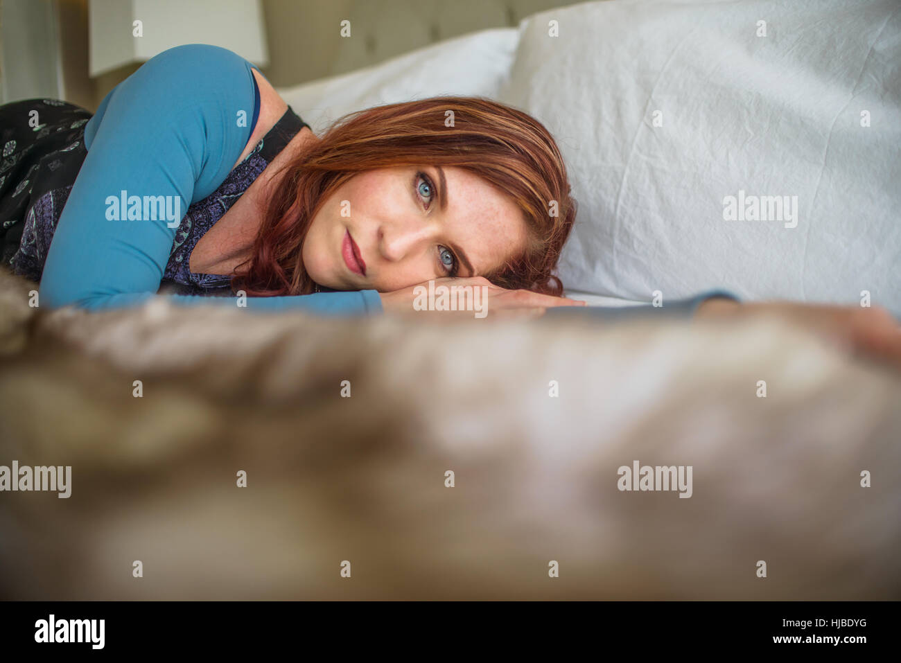 Woman lying in bed - Stock Image