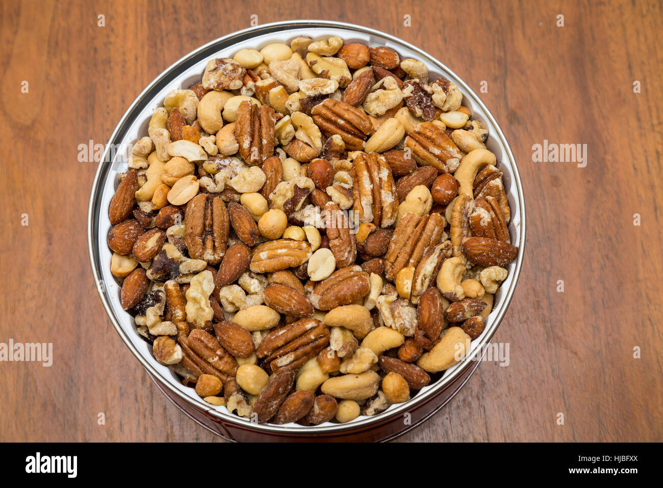 Deluxe round tin of mixed nuts on a wood table - Stock Image